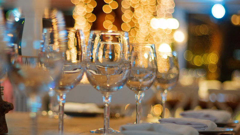Medium crop dining table glasses and soft focus lights   web page